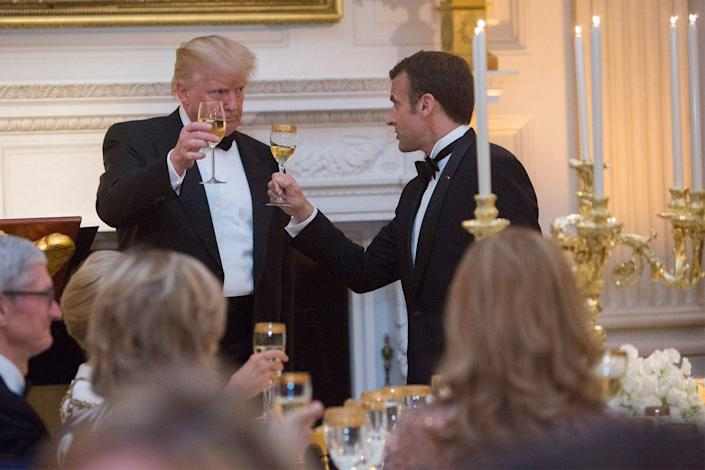 <p>During the event, both men shared a toast over what looks like a glass of white wine. Gold-adorned vessels complimented the ornate candlestick holders located on the head table. </p>