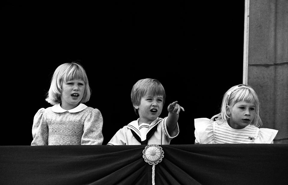 Prince William points to the fly-past alongside his cousins Zara Phillips (left) and Lady Rose Windsor (right) from the balcony. (PA Images)