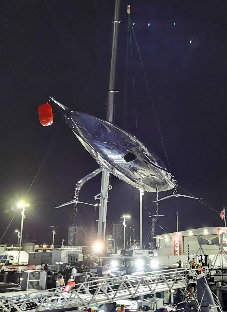 United States' American Magic's damaged boat, Patriot is lifted out of the water at its team base after it capsized during its race against Italy's Luna Rossa on the third day of racing of the America's Cup challenger series on Auckland's Waitemate Harbour, New Zealand, Sunday, Jan. 17, 2021. (Will Trafford/NZ Herald via AP)