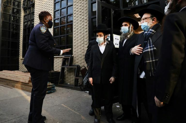 A New York police officer stands in front of a Satmar synagogue in October 2020, after a wedding in the Williamsburg area of Brooklyn of Brooklyn that was due to host 10,000 people was banned