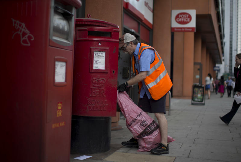 A postman empties a Royal Mail postbox outside a branch of the Post Office in London, Wednesday, July 10, 2013. The British government will lay out plans to privatize the Royal Mail in a 3 billion pounds ($4.5 billion) share offering that will see tens of thousands of workers get a stake in the company. The Communications Workers Union is opposed to the privatization amid fears that it will lead to job losses and lower wage increases. (AP Photo/Matt Dunham)