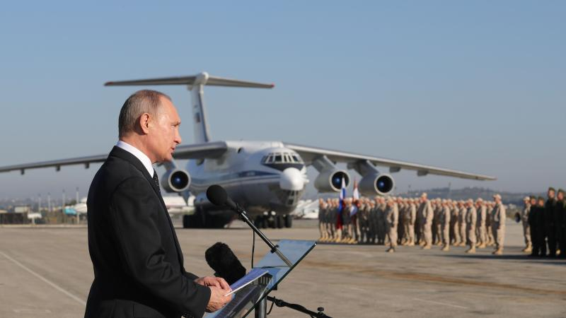 FILE - In this file photo taken on Tuesday, Dec. 12, 2017, Russian President Vladimir Putin addresses the troops at the Hemeimeem air base in Syria. Putin's approval ratings that top 80 percent make him all but certain to win another six-year term in the March 18 election. Just weeks after Russian President Vladimir Putin declared victory in Syria, Russian military outposts in the country have come under rebel attacks that are challenging Moscow's gains. (Mikhail Klimentyev/Pool Photo via AP, File)