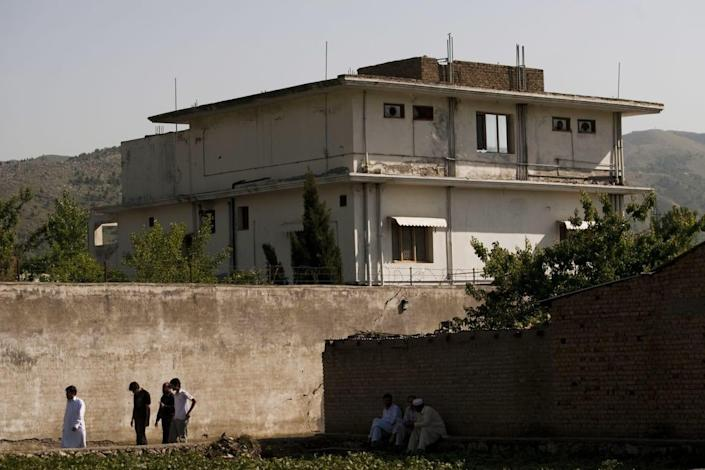 """<div class=""""inline-image__caption""""> <p>People walk past Osama Bin Laden's compound, where he was killed during a raid by U.S. special forces, May 3, 2011, in Abottabad, Pakistan. </p> </div> <div class=""""inline-image__credit""""> Getty </div>"""