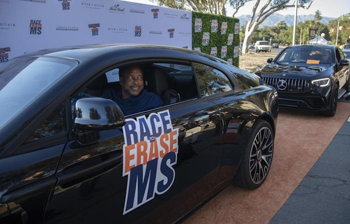 A car with smiling driver rolls in a procession along an orange roadway