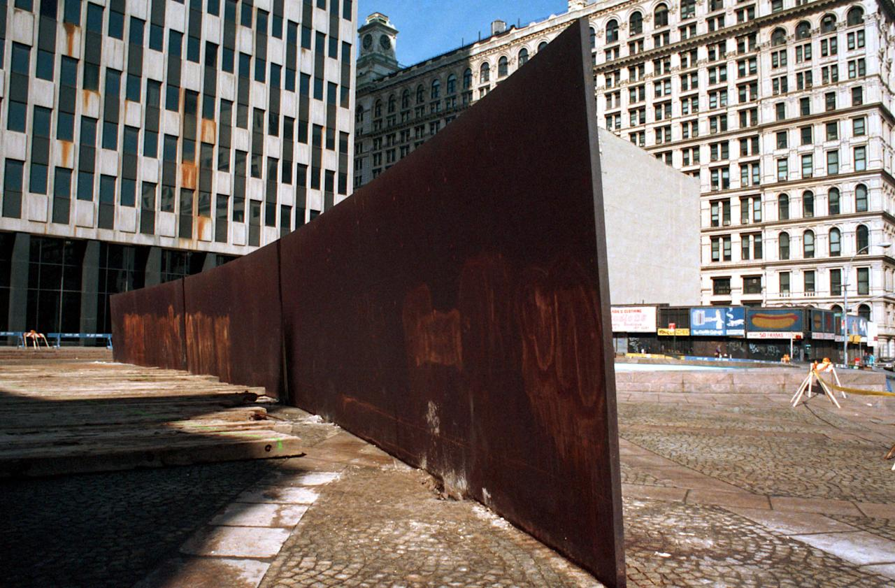 """**  FILE  **  """"Tilted Arc,"""" a 12-foot-high, curving, inclined wall of rusting steel by sculptor Richard Serra, awaits removal March 11, 1989, at Federal Plaza in lower Manhattan, New York. Controversy over the sculpture evoked warnings of censorship and art destruction from New York's art community while removal drew applause from many who considered the wall an eyesore. Serra is planning an almost similar scuplture at the California Institute of Technology campus in Pasadena, Calif. (AP Photo/Mario Cabrera)"""