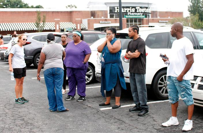 Anxious parents stand in the parking lot of a shopping center in Winston-Salem, N.C., on Wednesday, Sept. 1, 2021. One student was killed in a shooting at a North Carolina high school Wednesday and authorities were looking for the suspect, officials said.