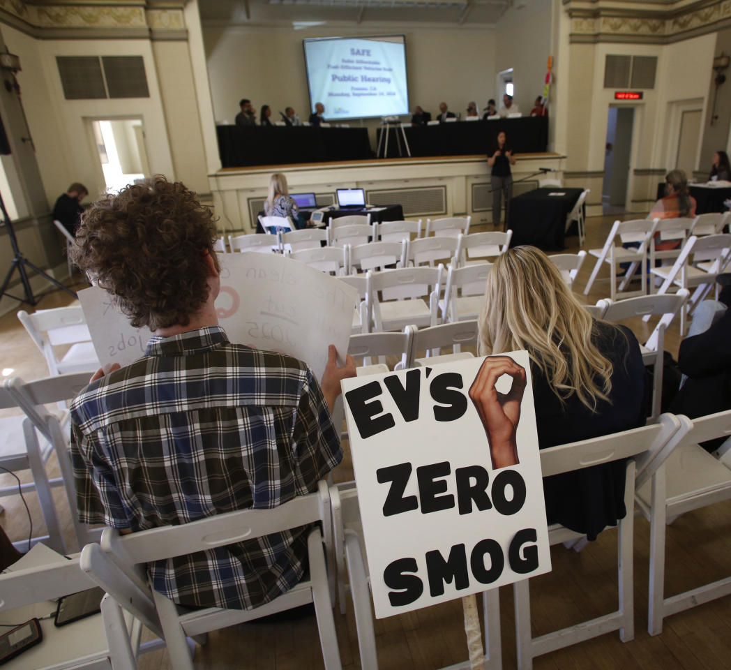 Benjamin Tuggy, left, listens to speakers during the first of three public hearings on the Trump administration's proposal to roll back car-mileage standards in a region with some of the nation's worst air pollution Monday, Sept. 24, 2018 in Fresno, Calif. The day-long session by the U.S. Environmental Protection Agency and National Highway Traffic Safety Administration is a means to gather public comment concerning the mileage plan, which would freeze U.S. mileage standards at levels mandated by the Obama administration for 2020, instead of letting them rise to 36 miles per gallon by 2025. (AP Photo/Gary Kazanjian)