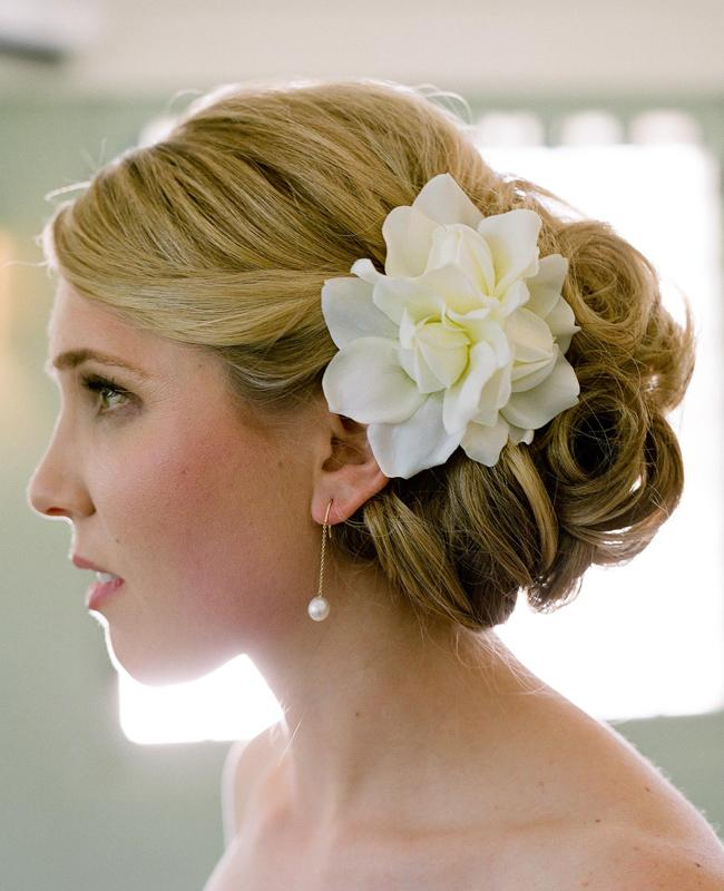 "<div class=""caption-credit"">Photo by: Q Weddings</div><div class=""caption-title""></div><b>On The Side Of A Classic Updo</b> Accessorize any type of bridal updo with flowers pinned on the side. The beauty in this style is its versatility: just about any type of flower works, you can choose any color, and there's no limit on how many or how few flowers you can use. <br>"