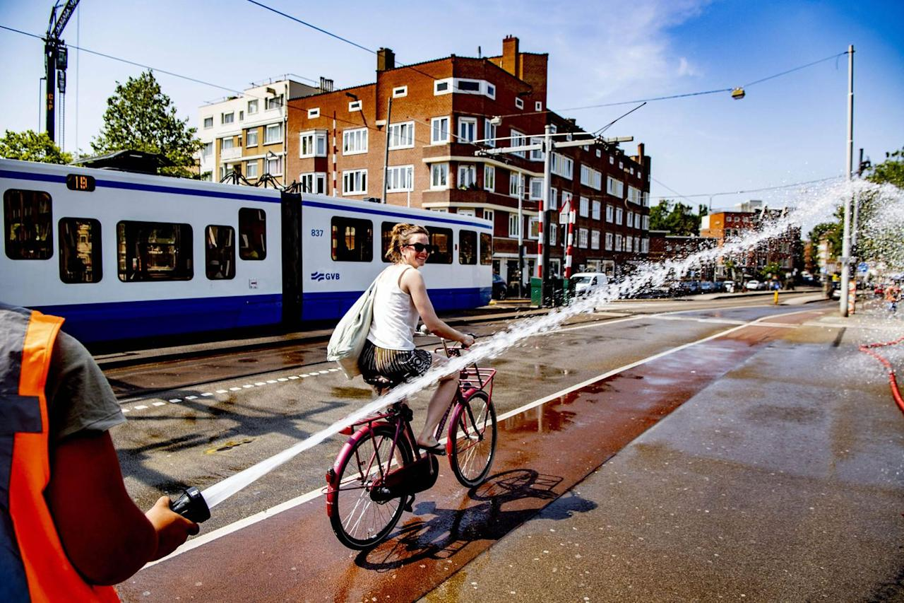 <p>Amidst Amsterstam's heatwave, a firefighter sprays water near a woman riding her bike on the Wiegbrug Bridge.</p>