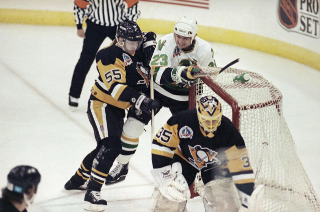 Minnesota North Stars' Brian Bellows (23) knocks the goal net off its post after he was sent crashing into it by Pittsburgh Penguins' Larry Murphy (55) as goalie Tom Barrasso guards during first period action of the Stanley Cup Game 6, May 25, 1991 in Bloomington, Minn. (AP Photo/Ann Heisenfelt)