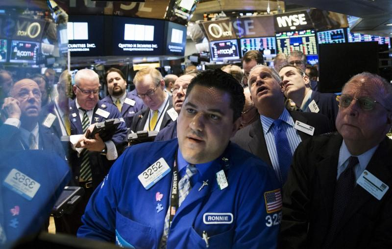 Traders wait for the opening of Whiting Petroleum's stock at the post where it's traded on the floor of the New York Stock Exchange