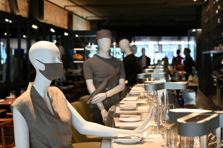 Mannequins are positioned to provide social distancing at the chic Le Monarque restaurant in Montreal on July 10, 2020; their clothes will be auctioned with proceeds going to charity