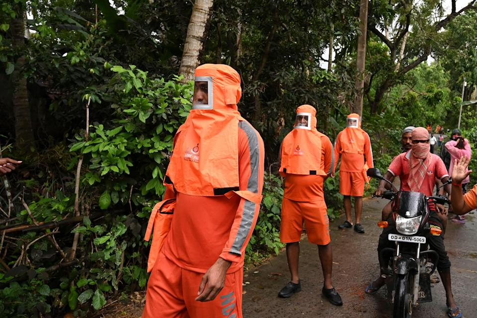 National Disaster Response Force personnel walk through a village and urge the villagers to evacuate (AFP via Getty Images)