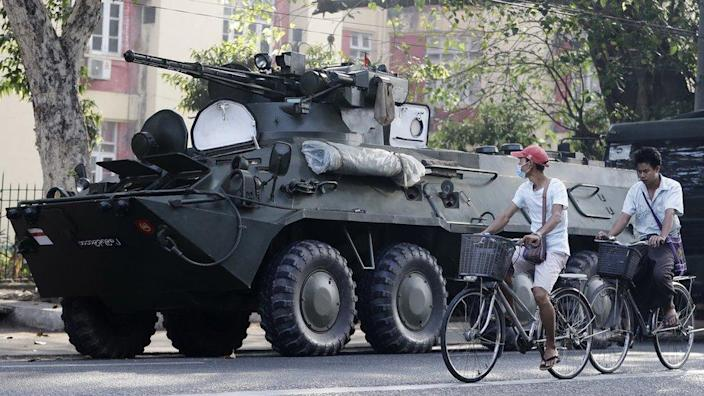People cycle past armoured vehicles stationed in front of the Central Women Hospital in Yangon, Myanmar, 15 February 2021.
