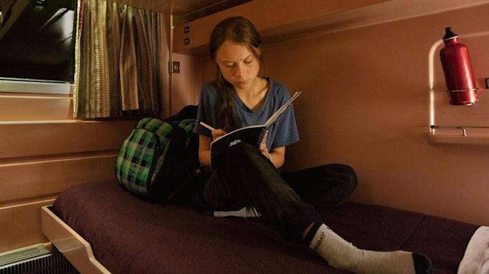 """Greta Thunberg writes in her journal on the train as she travels from Lisbon to Madrid for a U.N. climate conference on Dec. 5, 2019.<span class=""""copyright"""">Evgenia Arbugaeva for TIME</span>"""