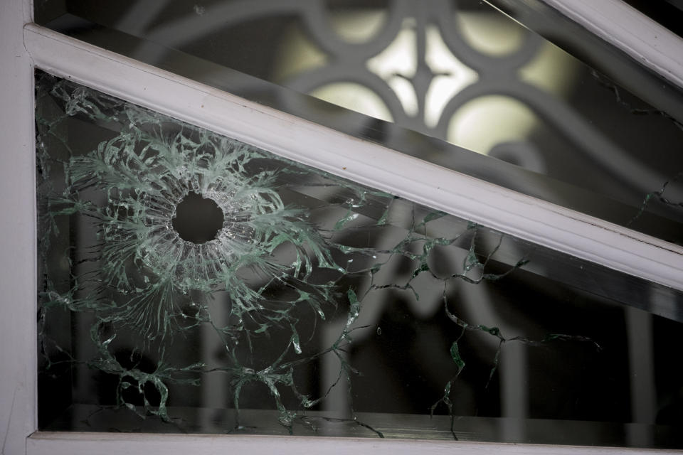 A bullet hole is visible in the front door of the Cuban Embassy in Washington, Friday, May 1, 2020, after a man opened fire with an assault rifle on Thursday morning. Officers found the suspect with an assault rifle and took the person into custody without incident, police said. (AP Photo/Andrew Harnik)