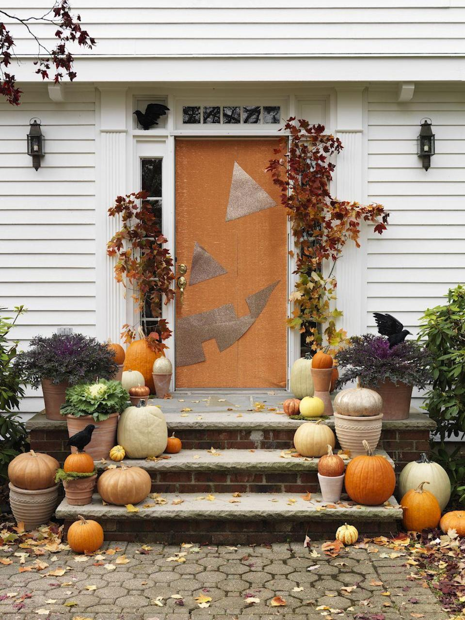 """<p>If you're pressed for time, go for a jack-o-lantern door. Begin by using masking tape to hang orange gift wrapping paper. Then, enhance the look by cutting an eye, nose, and mouth from gold paper. You can finish the look by adding tree branches, pumpkins, cabbages, and faux crows. <br><br><a class=""""link rapid-noclick-resp"""" href=""""https://www.amazon.com/JAM-PAPER-Gift-Wrap-Individually/dp/B01DAF8H8S?tag=syn-yahoo-20&ascsubtag=%5Bartid%7C10055.g.32948621%5Bsrc%7Cyahoo-us"""" rel=""""nofollow noopener"""" target=""""_blank"""" data-ylk=""""slk:SHOP ORANGE GIFT WRAP"""">SHOP ORANGE GIFT WRAP</a></p>"""