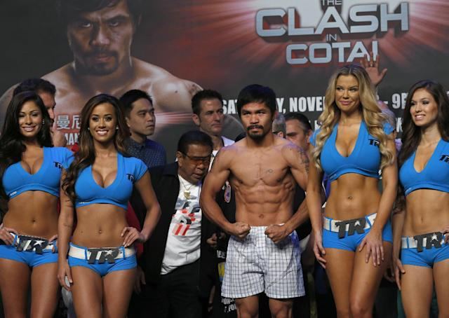 Filipino boxer Manny Pacquiao poses for photos during the weigh-in for his welterweight boxing fight against Brandon Rios of the United States at the Venetian Macao in Macau Saturday, Nov. 23, 2013. Pacquiao and Rios are scheduled to fight in their welterweight match at the casino on Nov. 24. (AP Photo/Vincent Yu)
