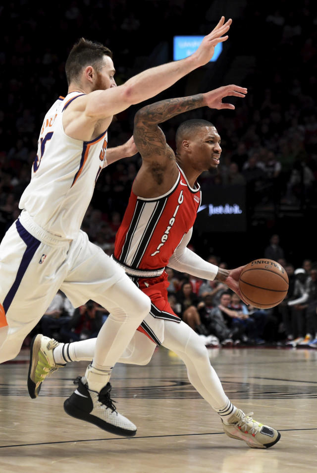 Portland Trail Blazers guard Damian Lillard, right, drives to the basket on Phoenix Suns center Aron Baynes, left, during the first quarter of an NBA basketball game in Portland, Ore., Tuesday, March 10, 2020. (AP Photo/Steve Dykes)
