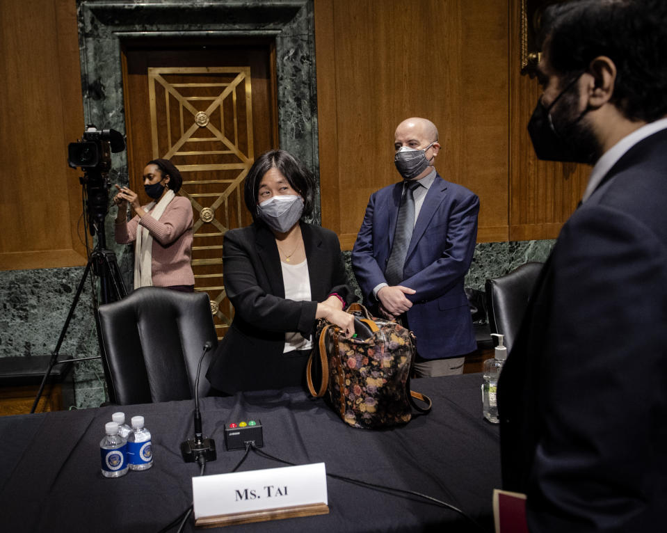 Katherine Tai, nominee for U.S. trade representative, packs up while her husband Robert Skidmore stands behind her after a Senate Finance Committee hearing on Capitol Hill, in Washington, Thursday, Feb. 25, 2021. (Bill O'Leary/The Washington Post via AP, Pool)