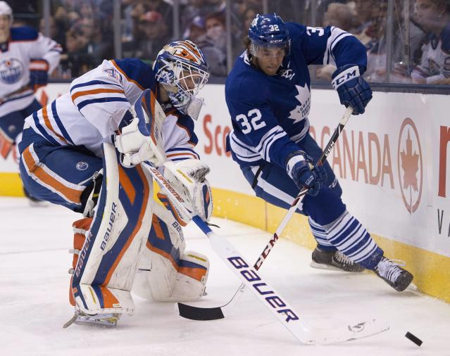 Toronto Maple Leafs Josh Leivo (32) and Edmonton Oilers goaltender Devan Dubnyk battle for the puck during the second period of an NHL hockey game, Saturday, Oct. 12, 2013 in Toronto. (AP Photo/The Canadian Press, Frank Gunn)