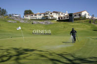 The pin flag for the 18th green bends over from the wind as a greenskeeper waters the grass after high winds suspended play during the third round of the Genesis Invitational golf tournament at Riviera Country Club, Saturday, Feb. 20, 2021, in the Pacific Palisades area of Los Angeles. (AP Photo/Ryan Kang)