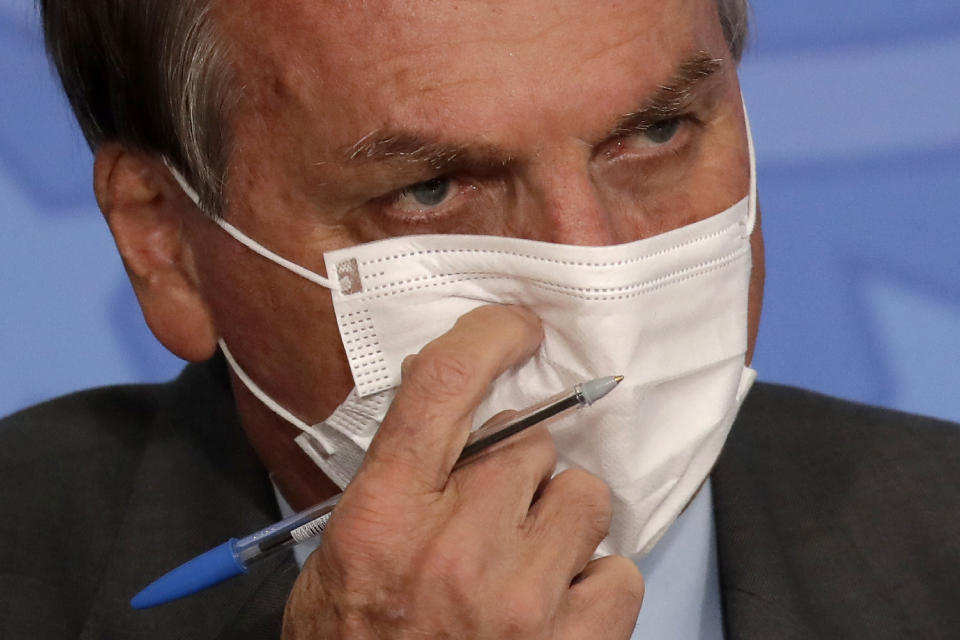 Brazil's President Jair Bolsonaro, wearing a mask to curb the spread of COVID-19, attends the launching ceremony of the Asphalt Giants Program, at the Planalto presidential palace, in Brasilia, Brazil, Tuesday, May 18, 2021. According to the Ministry of Infrastructure, the program offers facilities such as offering special lines of credit to purchase trucks or maintenance, predictability in the price of diesel oil, and faster vaccination of truck drivers against COVID-19. (AP Photo/Eraldo Peres)