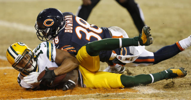 Green Bay Packers wide receiver Randall Cobb (18) dives into the end zone with the game-winning touchdown reception against Chicago Bears cornerback Zack Bowman (38) during the second half of an NFL football game, Sunday, Dec. 29, 2013, in Chicago. The Packers won 33-28 to capture the NFC North title. (AP Photo/Charles Rex Arbogast)