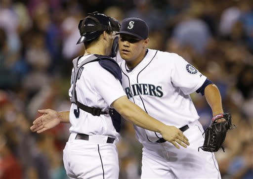 Seattle Mariners catcher Mike Zunino, left, and closing pitcher Yoervis Medina embrace after the team beat the Los Angeles Angels in a baseball game Saturday, July 13, 2013, in Seattle. The Mariners won 6-0. (AP Photo/Elaine Thompson)