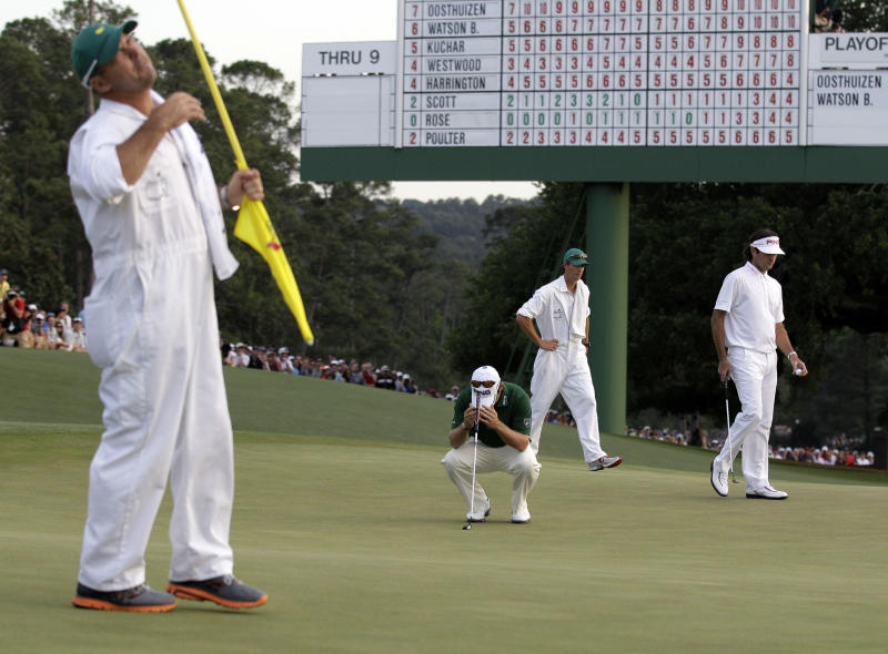 Louis Oosthuizen, of South Africa, and his caddie Wynand Stander react after Oosthuizen missed a birdie putt on the 18th hole during the fourth round of the Masters golf tournament Sunday, April 8, 2012, in Augusta, Ga. At right is Bubba Watson and his caddie Ted Scott. (AP Photo/Charlie Riedel)
