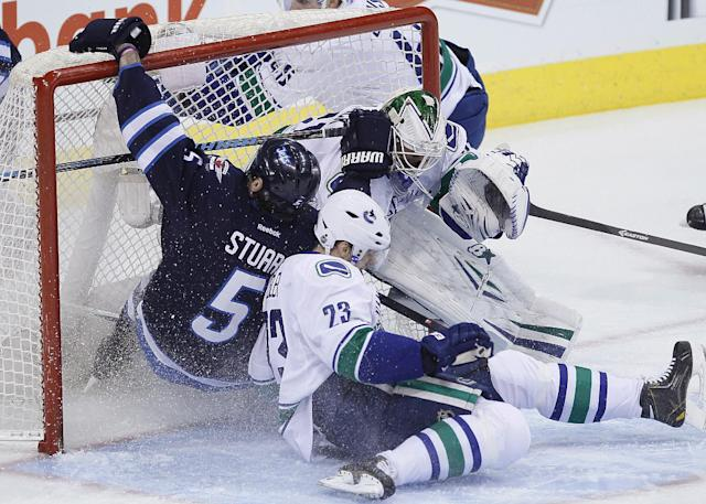 Winnipeg Jets' Mark Stuart (5) and Vancouver Canucks' Alexander Edler (23) crash into Canucks goaltender Eddie Lack during the first period of an NHL hockey game Wednesday, March 12, 2014, in Winnipeg, Manitoba. (AP Photo/The Canadian Press, John Woods)