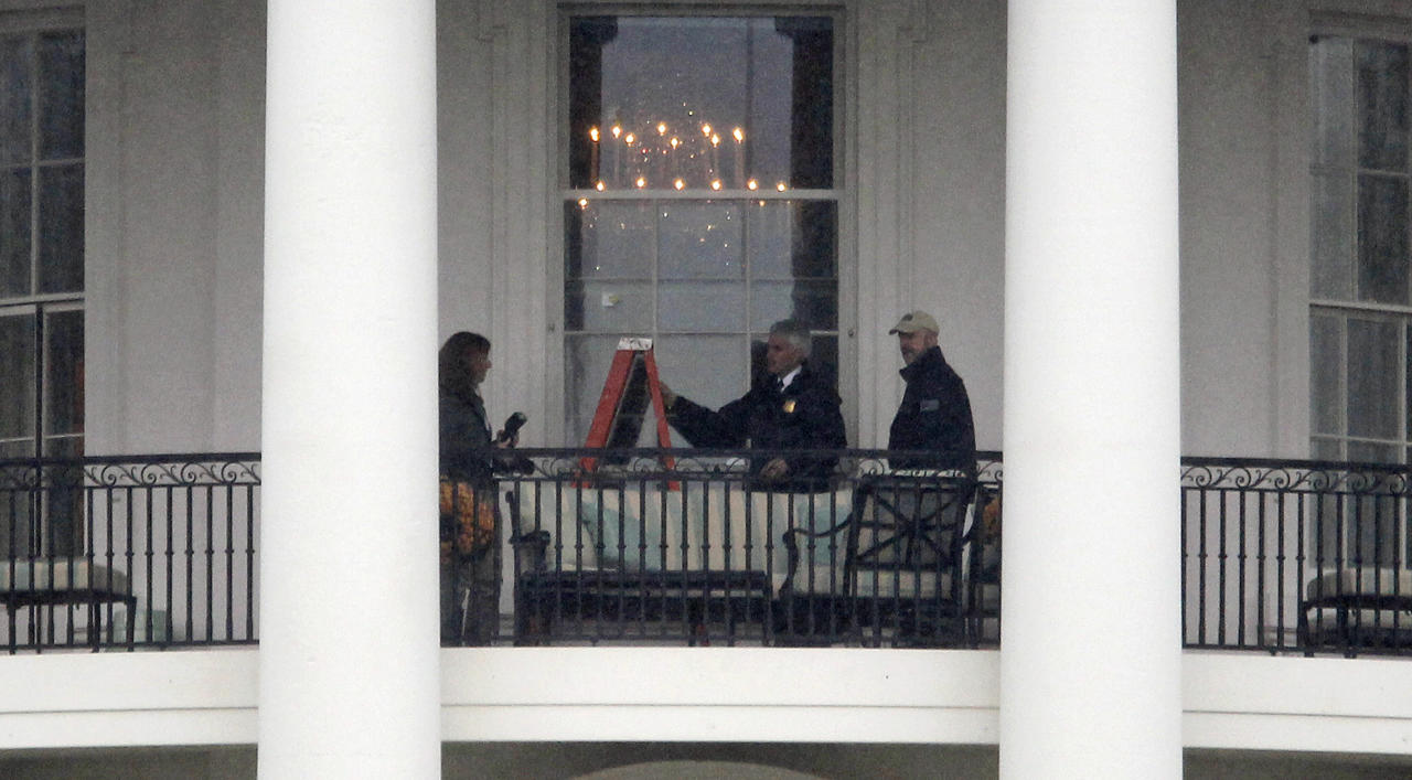 Law enforcement officers photograph a window at the White House in Washington, Wednesday, Nov. 16, 2011, as seen from the South Lawn. A bullet hit an exterior window of the White House and was stopped by ballistic glass, the Secret Service said. An additional round of ammunition was found on the White House exterior. The bullets were found Tuesday morning. (AP Photo/Haraz N. Ghanbari)