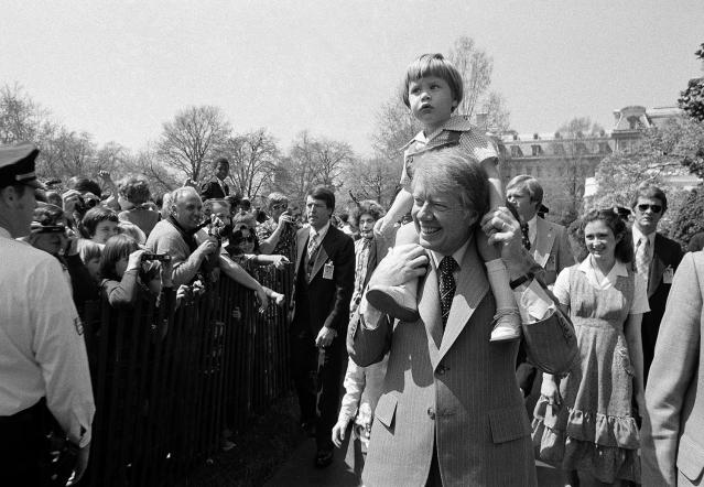 <p>President Jimmy Carter holds grandson Jason Carter, 2, on his shoulders while visiting the South Lawn on Monday, April 11, 1977, site of the Easter Egg Roll at the White House in Washington. (Photo: AP) </p>
