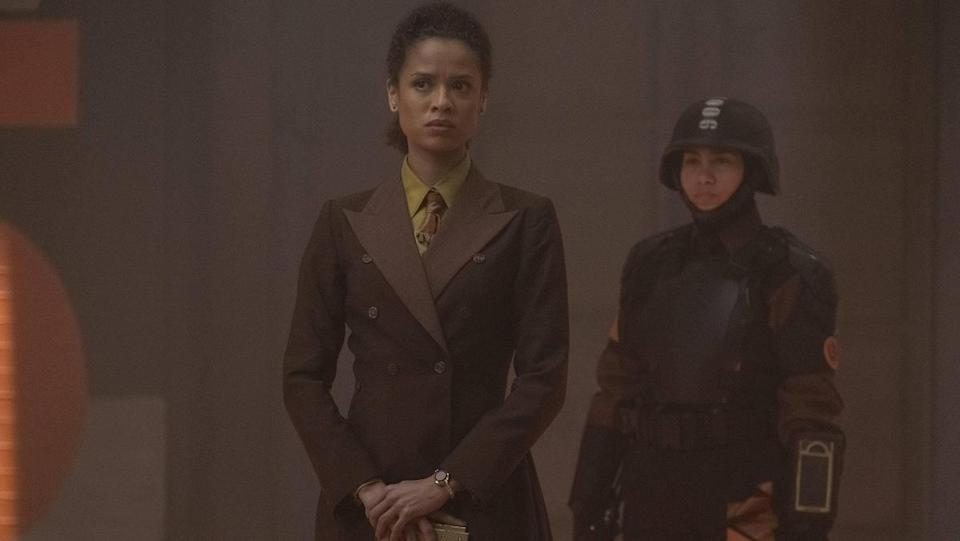 Renslayer (Gugu Mbatha-Raw) wearing a brown double-breasted suit and holding her Tempad, with another TVA agent behind her.