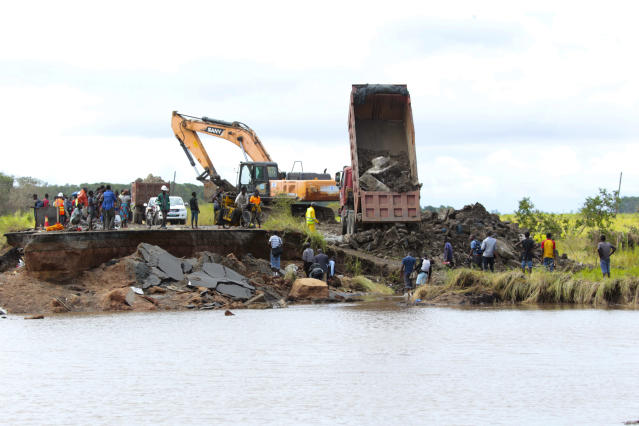 Construction vehicles at work near a section of the road damaged by Cyclone Idai in Nhamatanda about 50 kilometres from Beira, in Mozambique, Friday March, 22, 2019. As flood waters began to recede in parts of Mozambique on Friday, fears rose that the death toll could soar as bodies are revealed. (AP Photo/Tsvangirayi Mukwazhi)