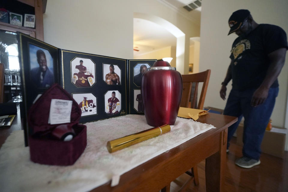Former U.S. Marine and retired law enforcement officer Marvin Wilson pauses next to an urn holding the ashes of his son along with photos of Tyrell Wilson in Fort Worth, Texas, Monday, May 17, 2021. Tyrell Wilson was shot and killed by Officer Andrew Hall in the San Francisco Bay Area just weeks before prosecutors charged the same officer with manslaughter and assault in the fatal shooting of an unarmed Filipino man more than two years earlier. (AP Photo/LM Otero)