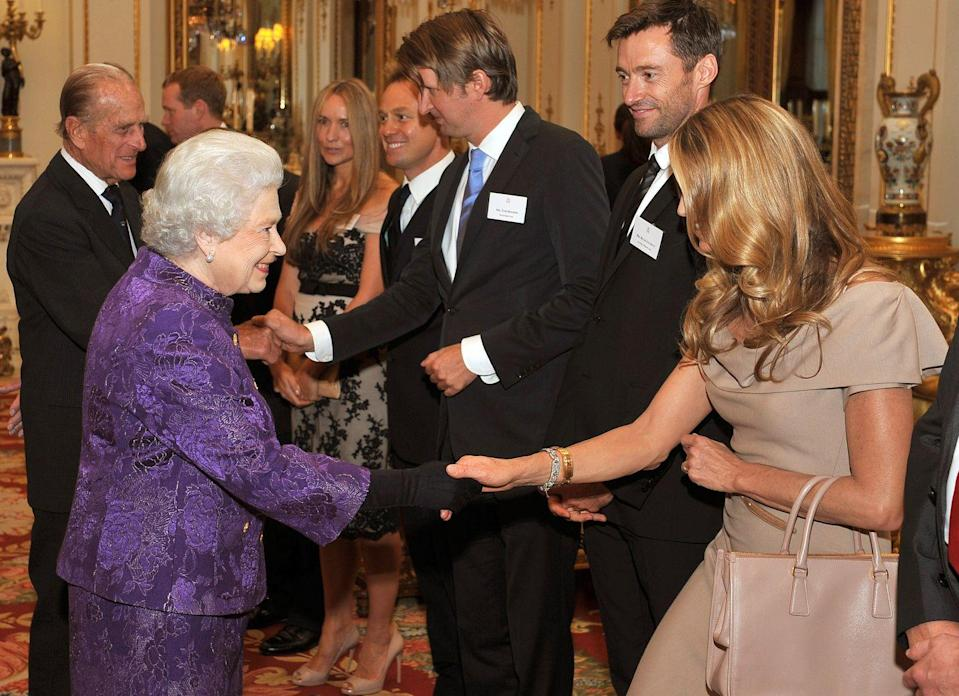 <p>Elle Macpherson looked modest next to Queen Elizabeth's bright purple ensemble during an event at Buckingham Palace in 2011. The Australian supermodel wore a monochrome outfit, pairing a beige dress with a nude handbag.</p>