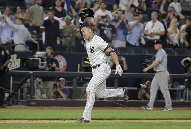New York Yankees' Giancarlo Stanton reacts as he rounds the bases after hitting a walk-off two-run home run during the ninth inning of a baseball game against the Seattle Mariners at Yankee Stadium Wednesday, June 20, 2018, in New York. The Yankees defeated the Mariners 7-5. (AP Photo/Seth Wenig)