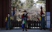 """Officials wearing traditional guard uniforms and masks stand in front of the Deoksu palace in downtown Seoul, South Korea, Sunday, Feb. 23, 2020. South Korea and China both reported a rise in new virus cases on Sunday, as the South Korean prime minister warned that the fast-spreading outbreak linked to a local church and a hospital in the country's southeast had entered a """"more grave stage."""" (AP Photo/Lee Jin-man)"""