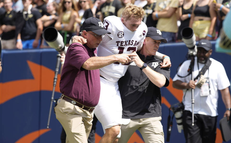 Texas A&M quarterback Haynes King, center, is helped off the field after being injured in the first half of an NCAA college football game against Colorado, Saturday, Sept. 11, 2021, in Denver. (AP Photo/David Zalubowski)