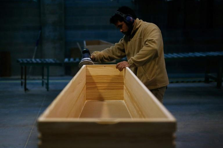 An employee polishes a coffin at the Eurocoffin factory in Barcelona on April 3, 2020