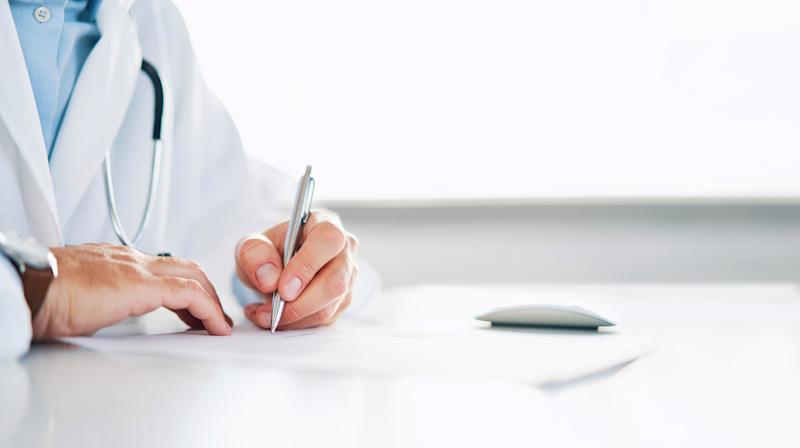 Close up of doctor signing prescription for patient