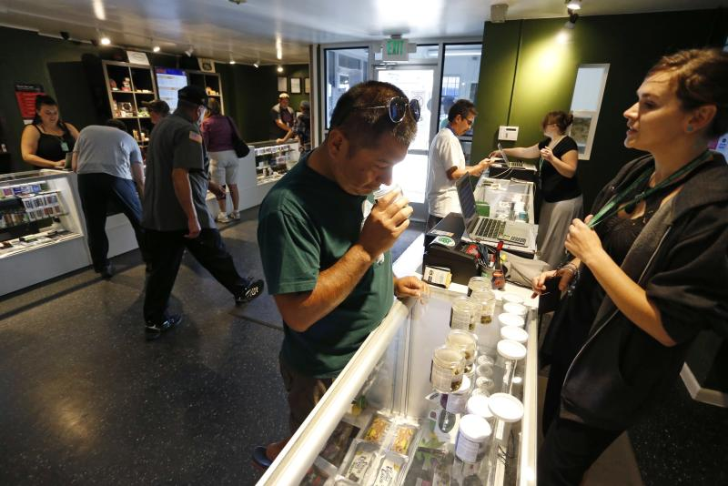 FILE- In this Sept. 16, 2015, file photo, customers shop for marijuana inside a recreational marijuana store in Denver. Sen. Elizabeth Warren, D-Mass., is leading a new effort to make sure vendors working with marijuana businesses don't have their banking services taken away. (AP Photo/Brennan Linsley, File)