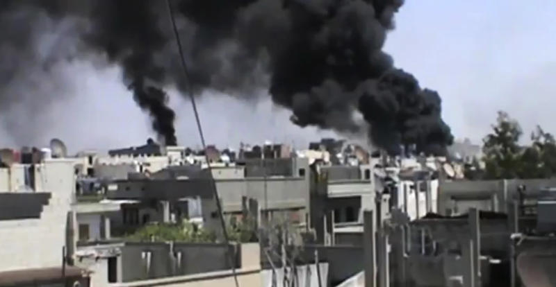 In this image made from amateur video released by the Shaam News Network and accessed Wednesday, April 18, 2012, black smoke rises from buildings in Khaldiyeh district, Homs, Syria. Nearly a week after a cease-fire took effect, Syrian troops pounded a rebel stronghold Wednesday as the country's foreign minister met with his Chinese counterpart in Beijing during the latest round of talks aimed at preventing the truce from unraveling. (AP Photo/Shaam News Network via AP video) TV OUT, THE ASSOCIATED PRESS CANNOT INDEPENDENTLY VERIFY THE CONTENT, DATE, LOCATION OR AUTHENTICITY OF THIS MATERIAL
