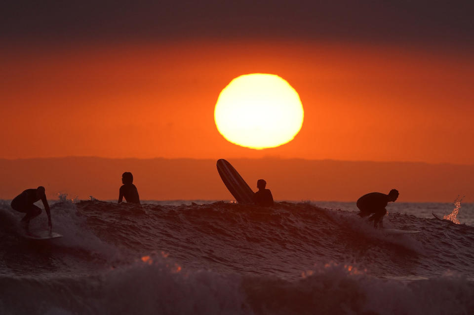 FILE - In this Thursday, April 30, 2020, file photo, Surfers ride as the sun goes down the day before the beach is scheduled to close during the coronavirus outbreak in Newport Beach, Calif. Californians headed to campgrounds, beaches and restaurants over the long holiday weekend as the state prepared to shed some of its coronavirus rules. (AP Photo/Mark J. Terrill, File)