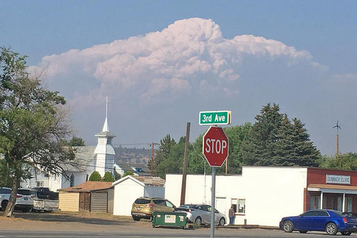 In this photo provided by the Bootleg Fire Incident Command, smoke from the Bootleg Fire rises behind the town of Bonanza, Ore., on Thursday, July 15, 2021. Firefighters scrambled Friday to control a raging inferno in southeastern Oregon that's spreading miles a day in windy conditions, one of numerous wildfires across the U.S. West that are straining resources. The Bootleg Fire, the largest wildfire burning in the U.S., has torched more than 377 square miles (976 square kilometers), and crews had little control of it. (Bootleg Fire Incident Command via AP)