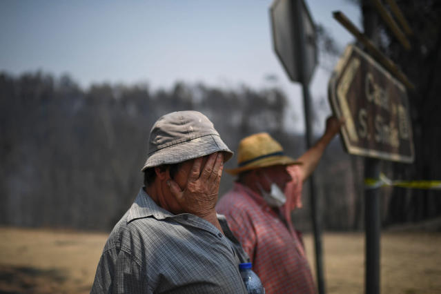 <p>A couple stands on the roadside watching firefighters pass by in Figueiro dos Vinhos, Portugal, June 18, 2017. Luisilda Malheiro, left, and Eduardo Abreu lost almost all the animals from their farm during a wildfire the previous night. (Patricia De Melo Moreira/AFP/Getty Images) </p>