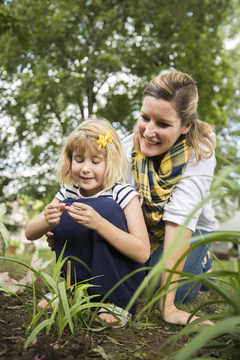 Laura Sullivan-Beckers and daughter Sylvie crouched next to garden bed
