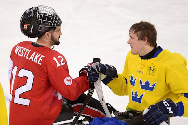 SOCHI, RUSSIA - MARCH 08: Greg Westlake of Canada shakes hands with Christian Hedberg of Sweden during the Preliminary Round Group A match between Canada and Sweden at Shayba Arena on March 8, 2014 in Sochi, Russia. (Photo by Dennis Grombkowski/Getty Images)
