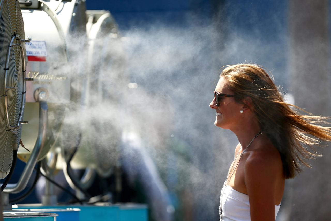 MELBOURNE, AUSTRALIA - JANUARY 14: A tennis fan cools off in front of a mister fan as Melbourne heads towards 43 degrees celsius (109 degrees fahrenheit) during day two of the 2014 Australian Open at Melbourne Park on January 14, 2014 in Melbourne, Australia. (Photo by Matt King/Getty Images)